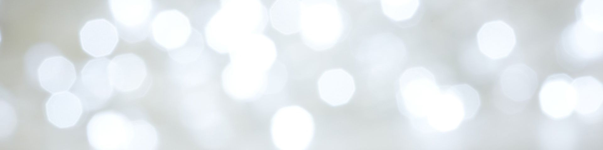 Dozens of lights, slightly blurred to create an abstract background in white and grey.